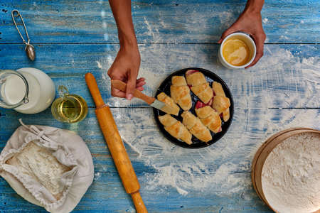smeared: Female hands smeared with egg cakes before you put it in the oven to bake, which lies next to a rolling pin rolling out dough for roguelike Stock Photo
