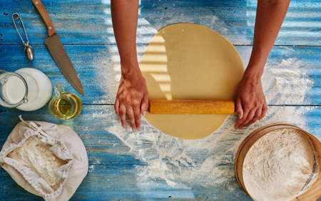 italian dish: Cook in a trendy Italian restaurant rolls the dough to cook from Spaghetti, Girl Roll out the dough to cook from it that pie fillings or pizza