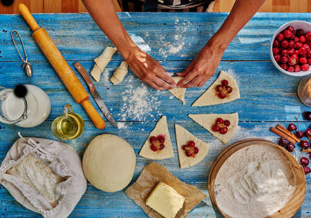 tucker: She lays cherry filling over the dough sprinkles brown sugar, it will be gentle bagels. On the table lay the dough cut into a triangular piece Stock Photo