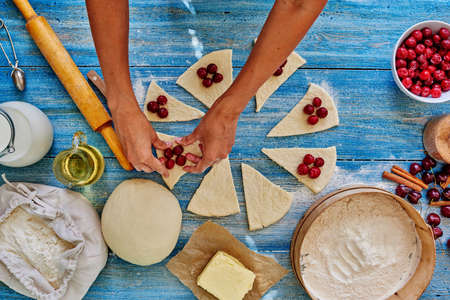 tucker: Girl assisent cook gently lay the puff pastry cherries, pitted, after the dough is wrapped
