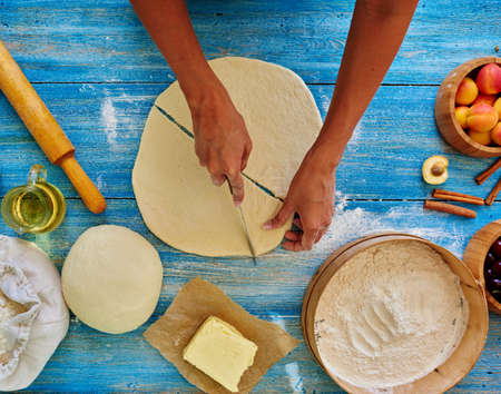cut up: In the frame of womens hands, cut up delicate dough into triangular pieces that would make them bagels fruit filling Stock Photo