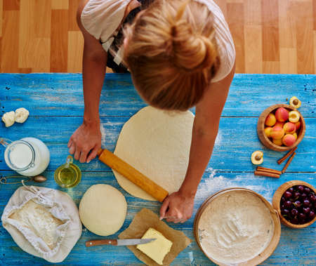 thinly: Girl assistant baker thinly rolled pastry to make him a cake with fruit
