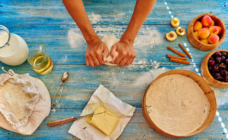 bakery products: Young girl chef kneads the dough  and rolled with a rolling pin and rolled Stock Photo