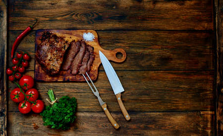 Appetizing piece of pork, chopped into small pieces, lying on a wooden table textural near cherry tomatoes as a garnish for baked meat
