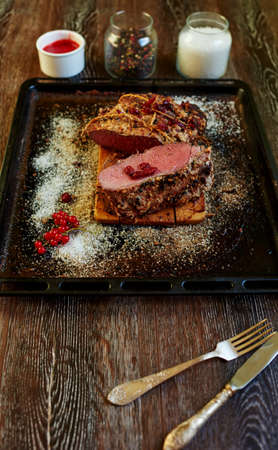 turned out: The trendy expensive steakhouse chef prepared a piece of pork tenderloin in the oven, the meat turned out medium rare places with blood for gourmets, the meat will cook the sauce of red berries Stock Photo