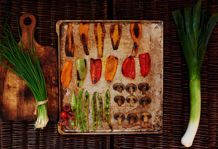 spread sheet: baked to a crisp vegetables spread out on a baking sheet in order, the two sides are two bundles of green onions Stock Photo