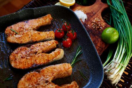 fish: Esposa espera a los hu�spedes para cocinar la cena para los filetes de salm�n, filetes de pescado son en la cacerola de la parrilla con romero y tomates, en una tabla de madera con una cacerola poner el pescado frito Foto de archivo