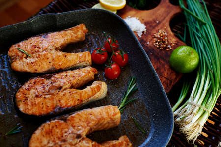 green fish: Wife waits for guests to cook for dinner salmon steaks,Fish steaks are on the grill pan with rosemary and tomatoes,On a wooden board with a pan put the fried fish Stock Photo