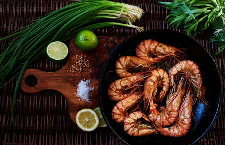 fried shrimp: Recent large king prawns cooked in a pan, lay next to lemon and lime, rosemary and chives, Best fried shrimp appetizer to the cold beer Stock Photo