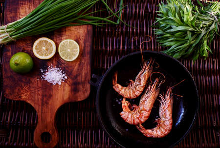 meat diet: The best snack to beer, prawns, grilled or rapid fire in a deep frying pan. Three large tiger shrimps lie in a deep bowl for dikustatsii near lemon and lime and rosemary