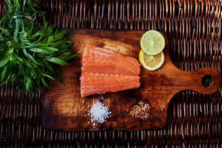 carb: Chef ready to pickle fresh salmon steak. A small piece of salmon is on the board for cutting meat and fish is scattered next to the salt and pepper Stock Photo