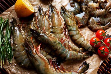 camaron: En la ventana del restaurante de pescado, es una variedad de camarones, langostinos, camarones pequeños en la composición concha decorado con tomates cherry y limón Foto de archivo