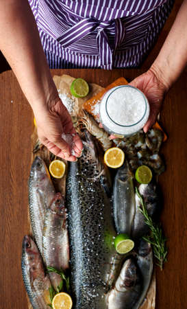 ooking: Female hand salted fish and home-cooked marinade, housewife preparing dinner for a large family Stock Photo