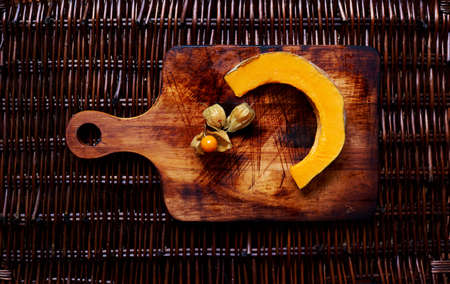 ut: Сut into slices the pumpkin lies on vintage wooden cutting board next to the cape gooseberry Stock Photo