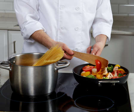 kitchen restaurant: Cook man standing near the plate, cook pasta and puts vegetables and mushrooms in a skillet