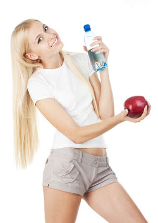 belonging to the caucasoid race: Sportswoman with a bottle of mineral water and red apple, isolated on white background Stock Photo