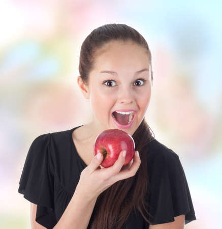 teenager fun eating a red apple, abstract background photo