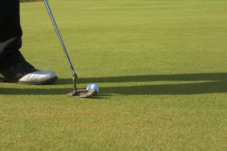 Golfer putting on the green, putter touching the ball. photo
