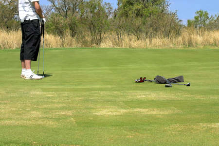 Golfer standing on the green with two golf clubs in his hand. Wet towel and another two golf clubs are lying next to him on the grass. Shot on South African golf course on a sunny day. photo