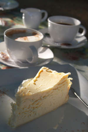 A cup of cappuccino with baked cheesecake, served on a square plate. Shallow depth of field - cake is in focus. Slight shadows because of evening light. Stock Photo