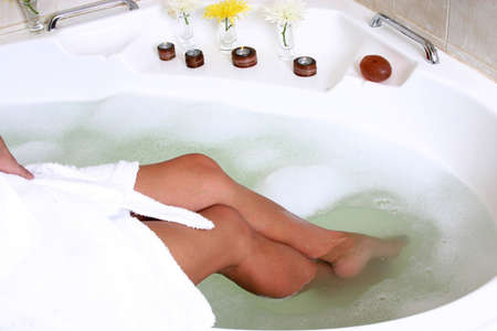 Sexy woman sitting in a bath full of bubbles, surrounded by flowers and candles