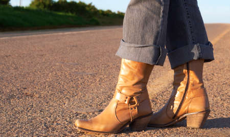 Woman wearing leather boots standing next to the road photo