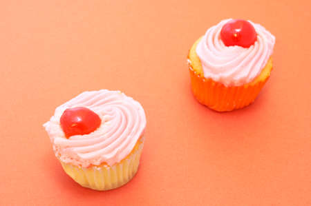 dainty: Two colorful vanilla cupcakes on orange paper background. Focus on front cupcake