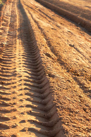 Dusty gravel road with tyre imprints , shot at sunset Stock Photo