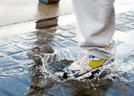 water shoes: Man stepping into a pool of water in a rush to get to his destination