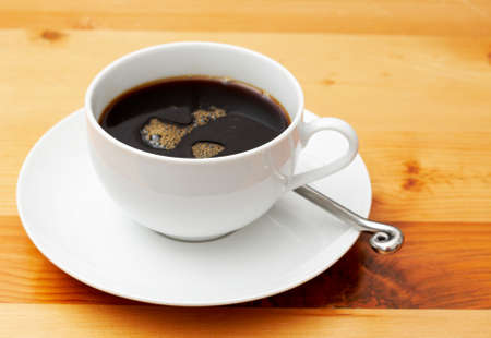 cater: Closeup of black coffee in a white cup. Shot on light wood background Stock Photo