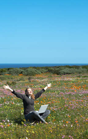 Blonde happy woman in casual clothes sitting in the field of flowers with her laptop photo