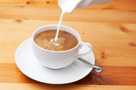 Closeup Kaffee mit Milch gegossen wird in die Tasse. Shot in hellem Holz Hintergrund