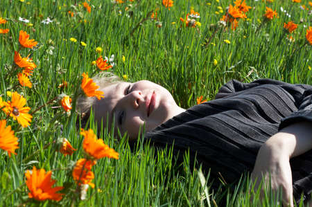 Blonde woman in casual clothes lying in a field of flowers  photo