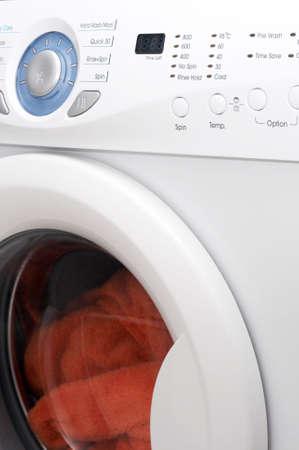 White washing machine with orange towels inside photo