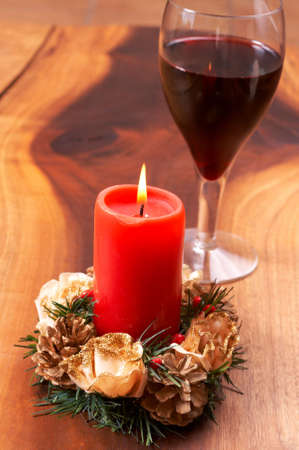 Christmas candle and a glass of wine on a wooden table photo