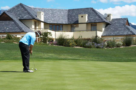 Golfer on the putting green next to a luxurious house Stock Photo