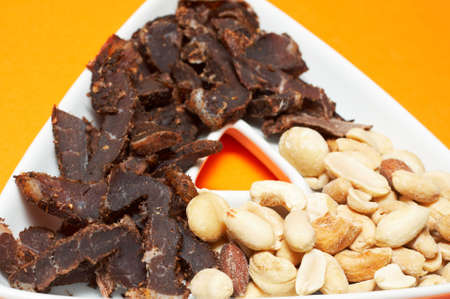 White triangle-shaped bowl with a selection of nuts and traditional South African biltong photo