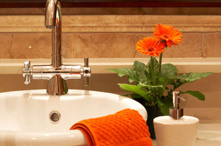 Beautiful sink in a bathroom with towel on it and a flower. Focus is on the tap Stock Photo