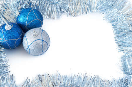 Three blue and silver Christmas baubles with silver tinsel forming a frame on white backgound photo