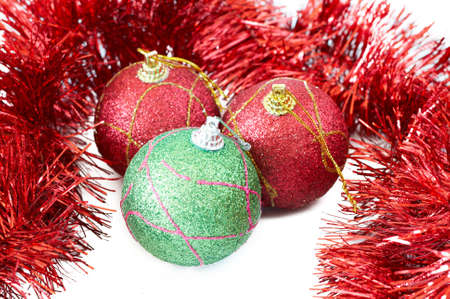 Three red and green Christmas baubles with red tinsel on white background photo