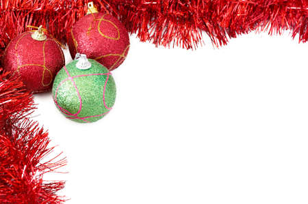 Three red and green Christmas baubles with red tinsel forming a frame on white backgound