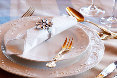 Table setting with golden cutlery and crystal glasses