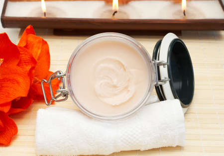 Relaxing spa scene with nourishing and exfoliating body scrub, white towel and candles in the background