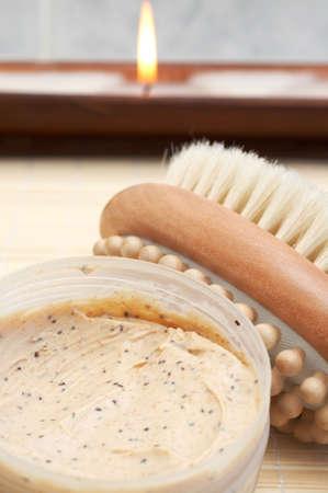 nourishing: Escena relajante spa con exfoliante y nutritivo cuerpo matorrales, cepillo masajeador y velas en el fondo