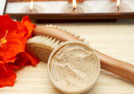 nourishing: Escena relajante spa con exfoliante y nutritivo cuerpo matorrales, cepillo masajeador de madera a la luz de fondo y velas  Foto de archivo