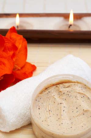 nourishing: La escena del balneario que relaja con el cuerpo de alimentaci�n y exfoliating friega, la toalla y las velas blancas en el fondo