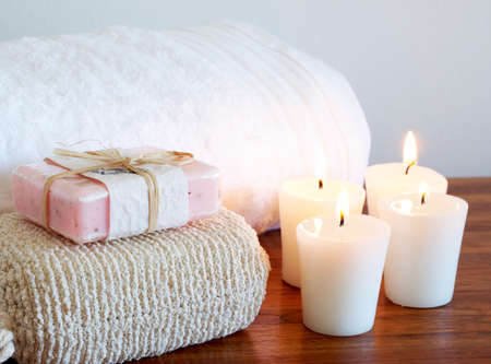 Relaxing spa scene with white fluffy towel, body sponge and handmade soap with candles in the background Stock Photo