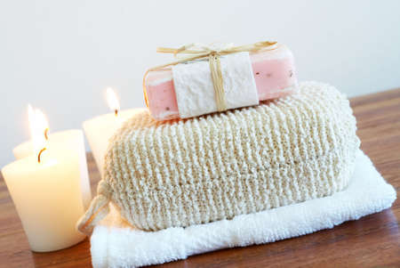 face cloth: Relaxing spa scene with exfoliating body sponge, handmade soap, white face cloth and candles in the background
