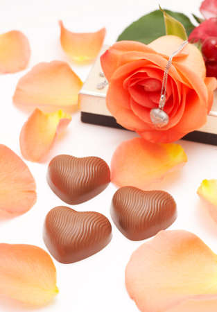 Valentines heart shaped chocolates with orange rose and silver necklace in the background, shot on white photo