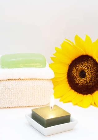 glycerin soap: Relaxing spa scene with body sponge, face towel, glycerin soap, candle and sunflower in the background